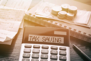 Tax savings written on calculator with tax files and money nearby